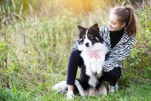 Slender girl sits next to her dog photo