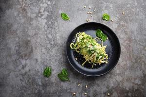 Spaghetti with spinach, pine nuts and parmesan cheese on a plate on a gray table photo
