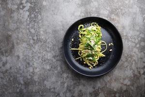 Spaghetti with spinach, pine nuts and parmesan cheese in a black plate on a gray table photo