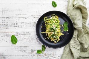 Italian spaghetti with spinach, pine nuts and parmesan on a light gray table photo