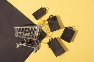 Flat lay miniature supermarket cart with shopping bags in black friday sale on yellow background photo