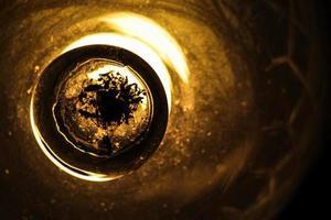 Cerca de una lámpara de cristal naranja antigua. hay insectos muertos en la parte inferior de la lámpara. fondo negro. foto