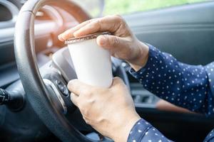 Asian lady holding coffee cup food for drink in car, dangerous and risk an accident. photo