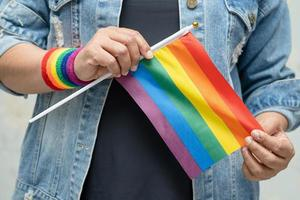 Asian lady wearing blue jean jacket or denim shirt and holding rainbow color flag, symbol of LGBT pride month celebrate annual in June social of gay, lesbian, bisexual, transgender, human rights. photo