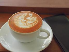 café con leche o capuchino con espuma espumosa, vista superior de la taza de café en la mesa de café. foto