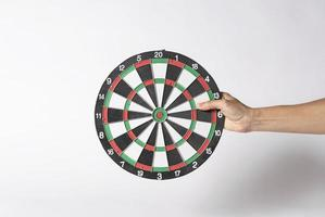 Hand holding target dart board on gray background. photo