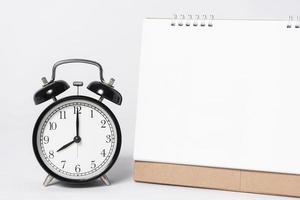 Calendario espiral de papel en blanco para publicidad de plantilla de maqueta y marca con reloj sobre fondo gris. foto