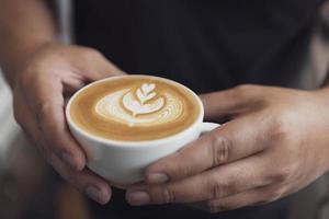 barista haciendo arte latte o capuchino con espuma espumosa, taza de café en la cafetería. foto