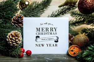 Christmas holiday greeting paper card design mockup with decoration on wood table. photo