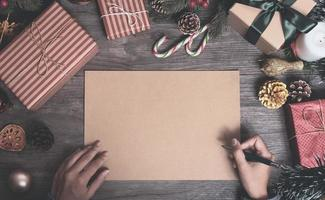 Christmas holiday greeting paper design mockup with decoration on wood table. photo