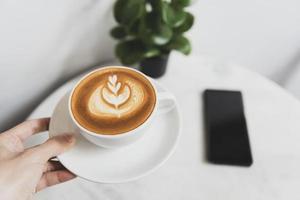 mano sosteniendo latte o capuchino con espuma espumosa, vista superior de la taza de café en la cafetería. foto
