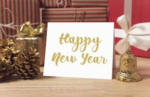 Happy new year holiday greeting paper card design mockup with decoration on wood table. photo