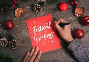 Hand writing greeting card Merry Christmas text with Christmas decoration on wood table. photo