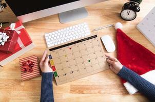 empresaria sosteniendo el planificador de calendario en vacaciones de Navidad en la oficina con decoración navideña en la mesa. foto