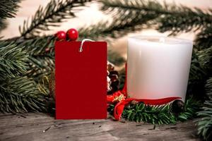 mockup tag paper card with candle christmas decoration on wood table background. photo