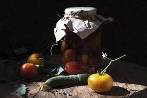 Canned vegetables tomatoes in a glass jar on a dark wooden background. Fresh vegetables on a wooden table. Still life photo