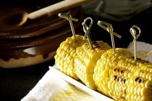 Roasted corncob on wooden table photo
