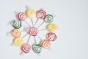 Colorful circle with green, red, yellow and orange lollipops. White background photo