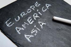 Small blackboard with continents handwritten in chalk, europe, america, asia photo