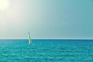 Pequeño velero personal navegando en mar abierto y plano en un día de verano foto