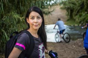 Woman riding a bicycle in the countryside and looking at camera photo