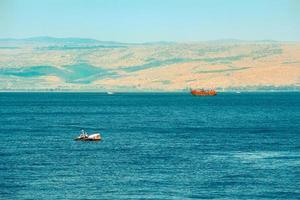 Barco de madera marrón navegando en el mar de Galilea. foto