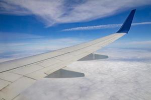 Airplane wing on the sky and over sea with clouds photo