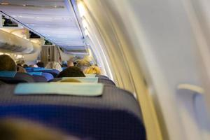 Interior of passenger airplane with people on seats photo