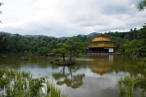 Beautiful view of Golden Temple and the lake and forest around it. Cloudy day, no people. Kyoto, Japan photo