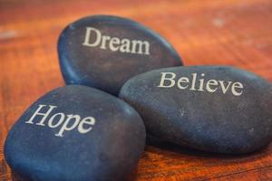 Black inspirational pebble stones with the words Dream, Believe and Hope on wooden background photo