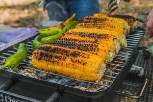 Corn and green chili pepper are cooked on the grill photo