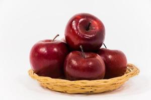 Close up of ripe red apples in wicker basket isolated on white background photo