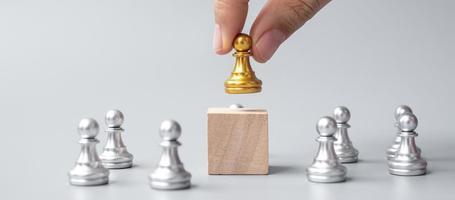 mano sosteniendo piezas de peón de ajedrez dorado o empresario líder con hombres de plata. concepto de victoria, liderazgo, éxito empresarial, equipo, reclutamiento y trabajo en equipo foto