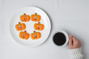 woman hand holding coffee cup during eating funny Halloween Cookies. Happy Halloween day, Trick or Threat, Hello October, fall autumn, Traditional, party and holiday concept photo