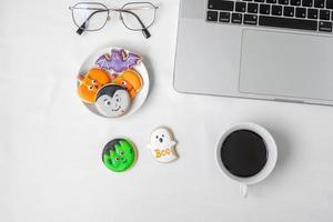 Halloween Cookies,  hot coffee and computer laptop on white background. Happy Halloween, online shopping, Hello October, fall autumn, Festive, party and holiday concept photo