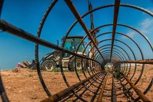 Workers and a tractor with a drilling device at a construction site - view from inside construction steel rod photo