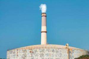 The chimney of the Tel Aviv Reading power plant near a large natural gas storage tank photo