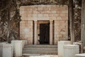 Entrance to an old small private bricks stone tomb carved into the mountain in israel photo