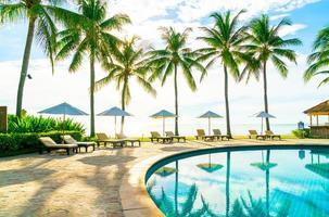 Hermosa sombrilla de lujo y una silla alrededor de la piscina al aire libre en el hotel y resort con palmera de coco en el cielo azul foto