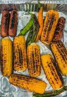 Top view of grilled corn cobs, green chili pepper and sausages on disposable aluminum  food packaging photo