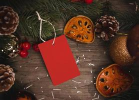 mockup tag paper card with pine cones christmas decoration on wood table background. photo
