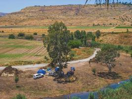 Landscape of country area of Jordan Valley in Israel with a group of people camping photo