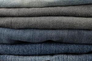 Stack of various shades of blue jeans trousers at white background photo