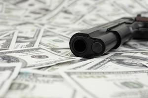 Pistola pistola negra en la pila de dinero 100 dólares antecedentes foto