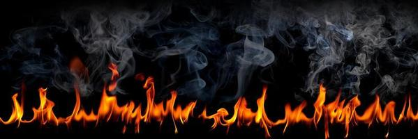llamas de fuego con humo sobre fondo negro, chispas ardientes al rojo vivo se elevan, partículas voladoras brillantes de color naranja ardiente foto