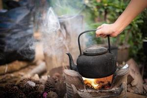 Close up hand holding boil water old kettle on the fire with a charcoal stove at blurred background photo