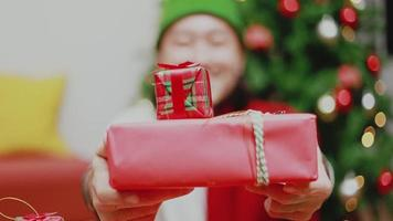 Asian man presents a red gift box in front of the camera. video