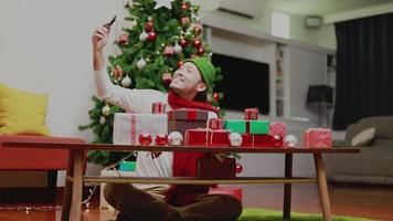 Asian men using mobile having video chat showing gift box to friends decorate Christmas tree celebrates the new year.