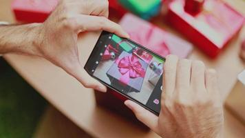 Asian men taking a photo gift box on smartphone decorate Christmas tree celebrates the new year in the living room at home. video
