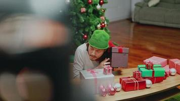 Asian men checking the gift box in the living room having a Christmas tree celebrates the new year at home. video